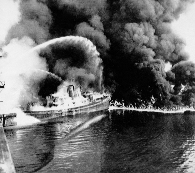 This black and white picture shows a tugboat on fire. Thick black smoke fills the air while streams of water from fire houses try to douse the flames.